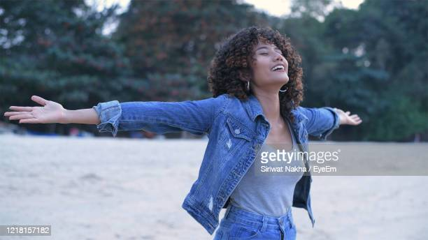 young woman standing with arms outstretched at beach - bras humain photos et images de collection