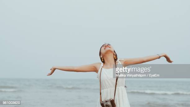 Young Woman Standing With Arms Outstretched By Sea Against Clear Sky