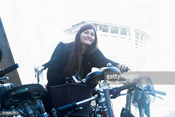 young woman standing with bicycle in parking lot, freiburg im breisgau, baden-w��rttemberg, germany - sigrid gombert fotografías e imágenes de stock