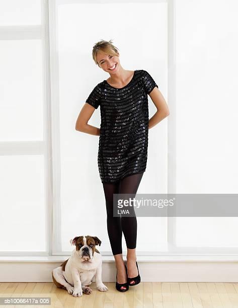 young woman standing with dog, smiling, portrait - gedomesticeerde dieren stockfoto's en -beelden