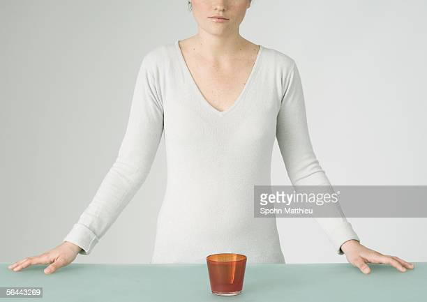 young woman standing with glass in front of her on table, partial view - vネック ストックフォトと画像