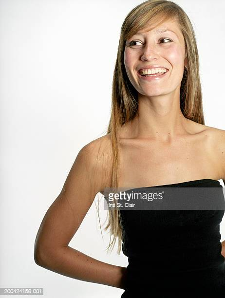 Young woman standing with hands behind back, smiling, looking away