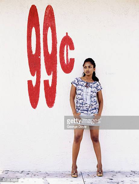 young woman standing with her back at a wall - african prostitutes stock photos and pictures