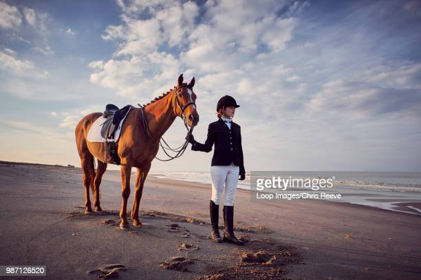 a young woman standing with her horse on the beach - riding hat stock pictures, royalty-free photos & images