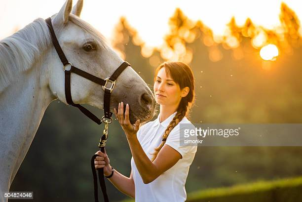 Young woman standing with horse