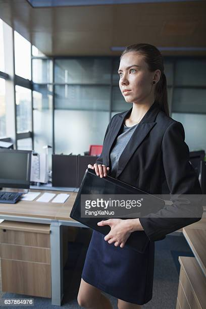 Young woman standing with laptop in business office