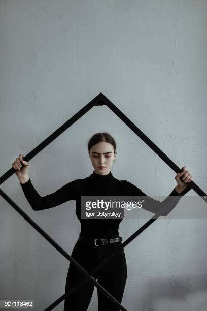young woman standing with large picture frame - female models photo gallery stock photos and pictures