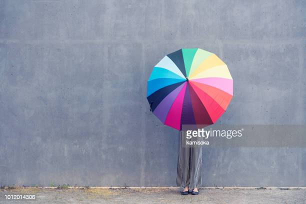 young woman standing with multicolored umbrella in front of a concrete wall - multi coloured stock pictures, royalty-free photos & images