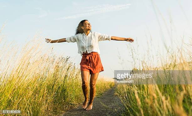young woman standing with outstretched arms on path in field - barfuß stock-fotos und bilder