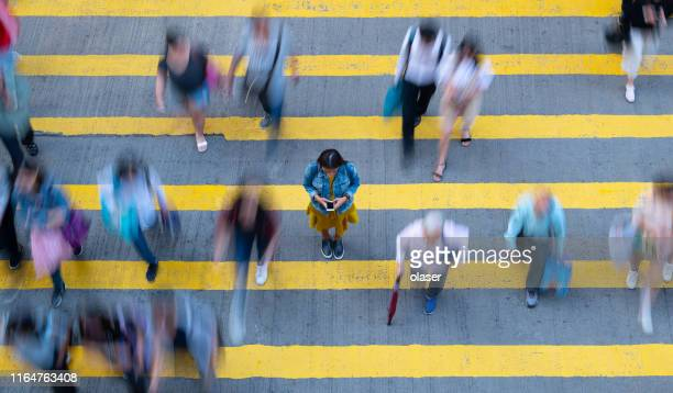young woman standing, with phone, in motion blurred crowd - surrounding stock pictures, royalty-free photos & images