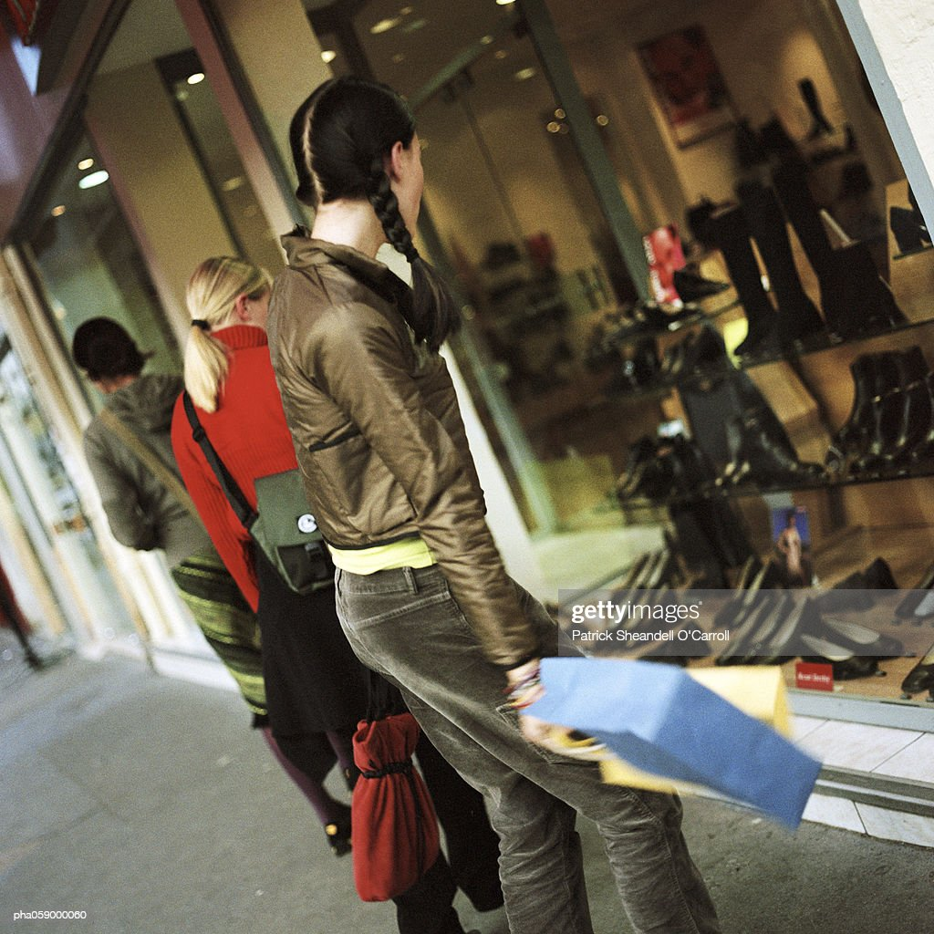 Young woman standing with shopping bag in front of shop window, side view, two other people in background : Stockfoto