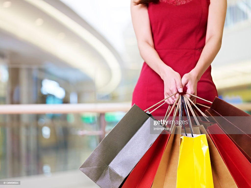 young woman standing with shopping bags in hands : Stock Photo