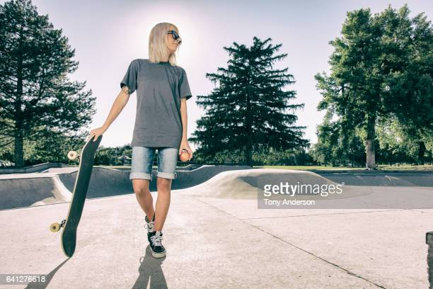 Young woman standing with skateboard at skatepark