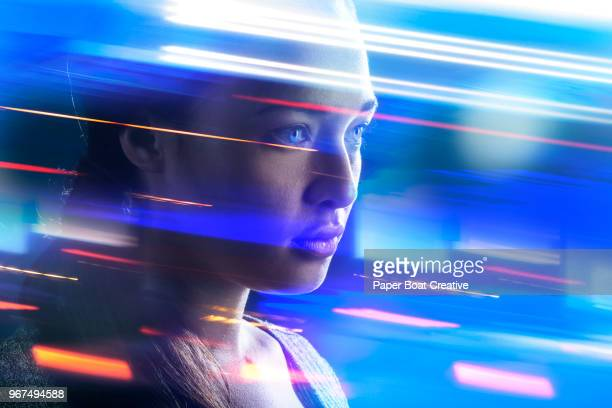 young woman standing with speeding lights swirling around her - licht natuurlijk fenomeen stockfoto's en -beelden