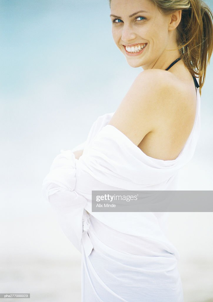 Young woman standing wrapped in towel, smiling at camera : Stockfoto
