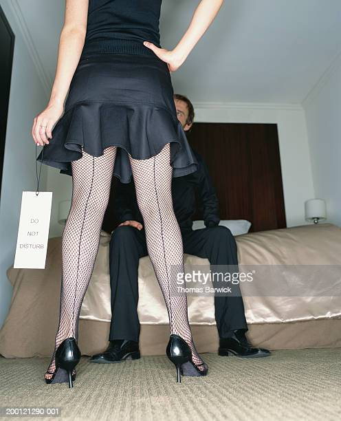 Young woman standing, young man waiting on bed in hotel room