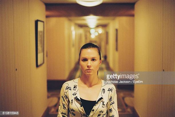 A young woman stands alone in an empty hallway