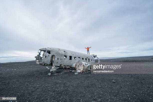 Young woman stands arms outstretched on airplane crashed on black sand beach looking around her contemplating surroundings