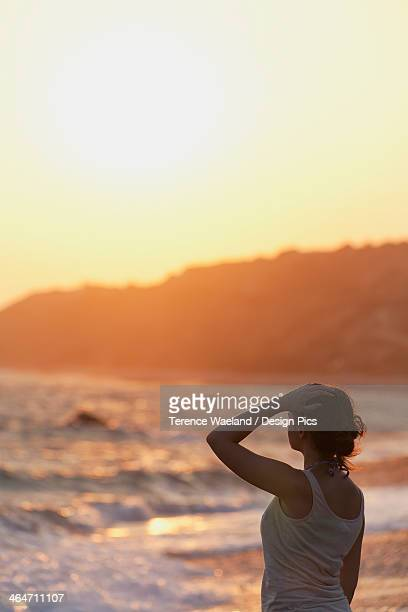 a young woman stands at the water's edge watching the sunset - terence waeland stock pictures, royalty-free photos & images
