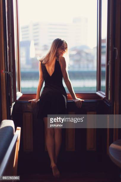Young woman stands at window