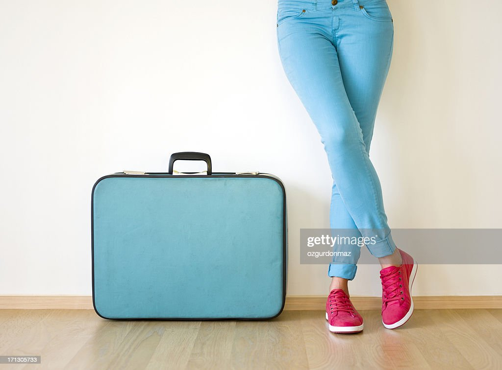 Young woman stands beside suitcase : Stock Photo