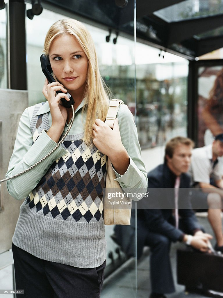 Young Woman Stands by a Bus Stop Talking on a Pay Phone : Stock Photo