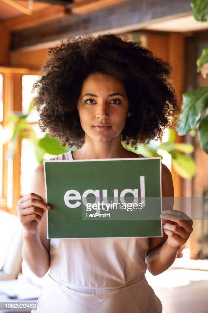 young woman stands for equal rights. - black civil rights stock pictures, royalty-free photos & images