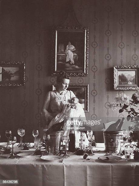 A young woman stands holding a baby next to an array of empty bottles and half finished glasses of wine circa 1890