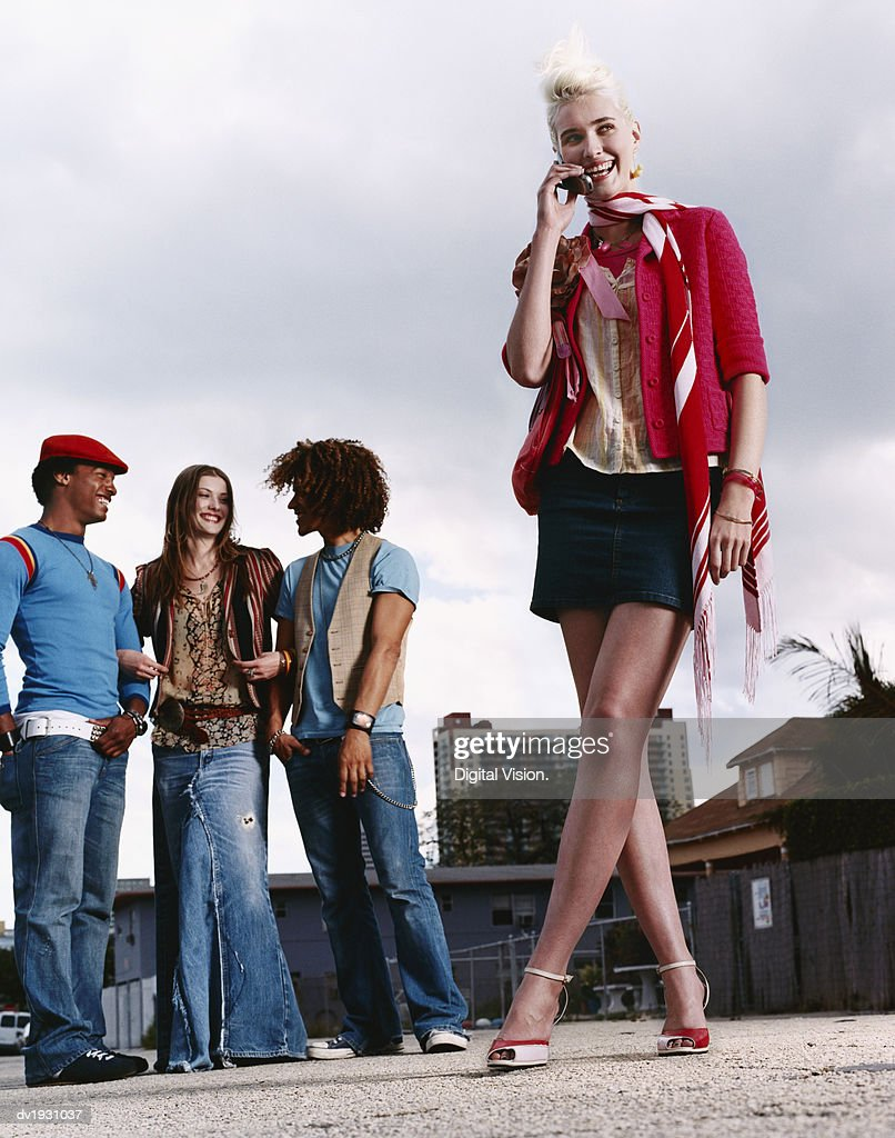 Young Woman Stands in an Urban Setting Talking on Her Mobile Phone, Her Friends in the Background : Stock Photo