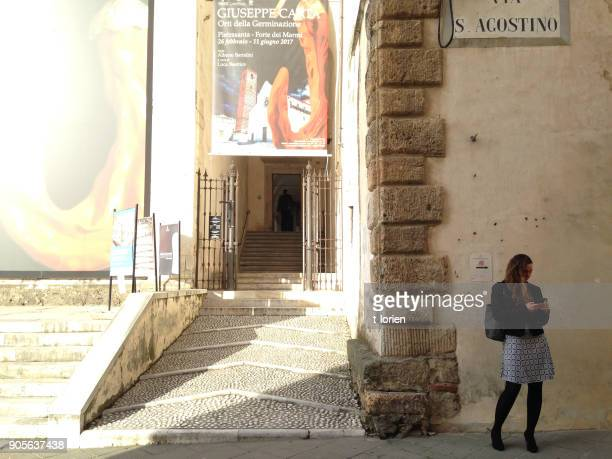 Young woman stands in front of public library in Tuscany.