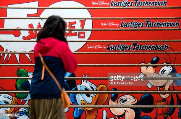 A young woman stands in front of stairs which have been covered with an advert to mark the 50th anniversary of the German version of the Donald Duck...
