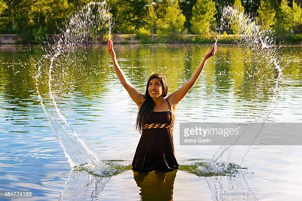 Young woman stands in lake and splashes water