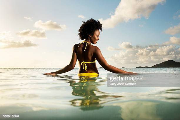 Young woman stands in sea with hands on surface.