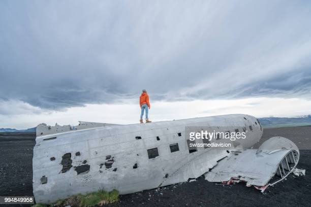 Young woman stands on airplane crashed on black sand beach looking around her contemplating surroundings