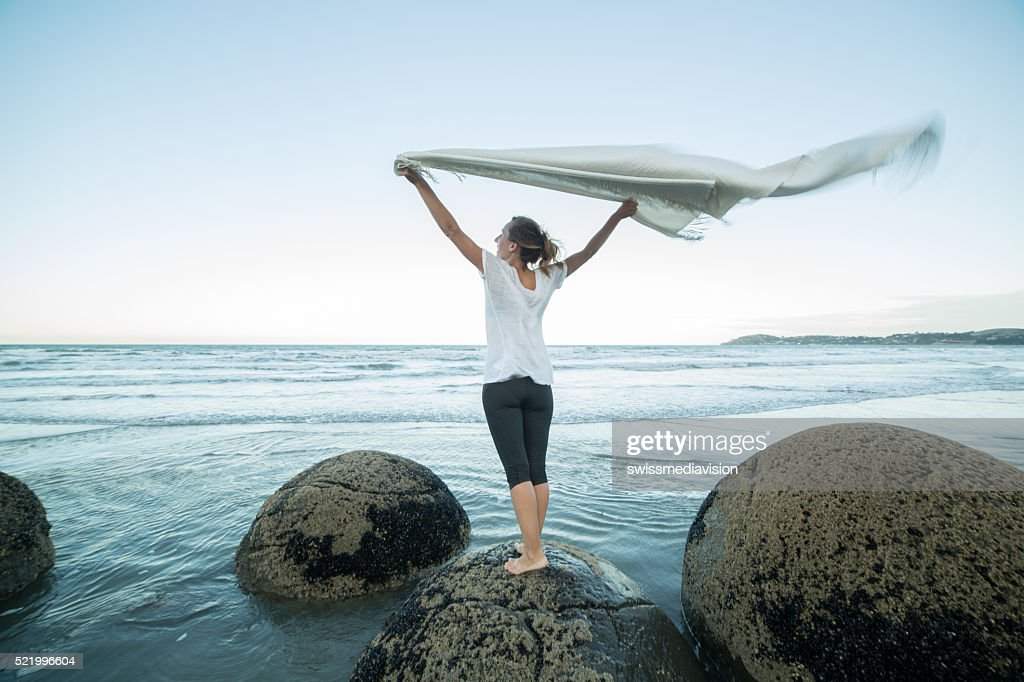 Young woman stands on boulder, holds blanket in the air : Stock Photo