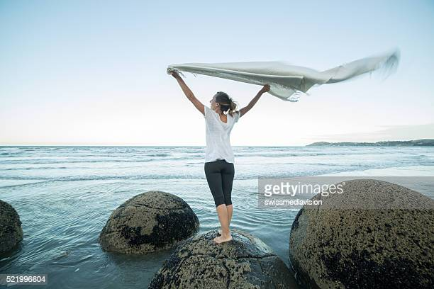 Young woman stands on boulder, holds blanket in the air