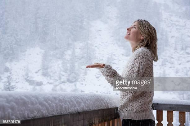 Junge Frau steht auf deck, Uhren Schneeflocken fallen bei Schnee