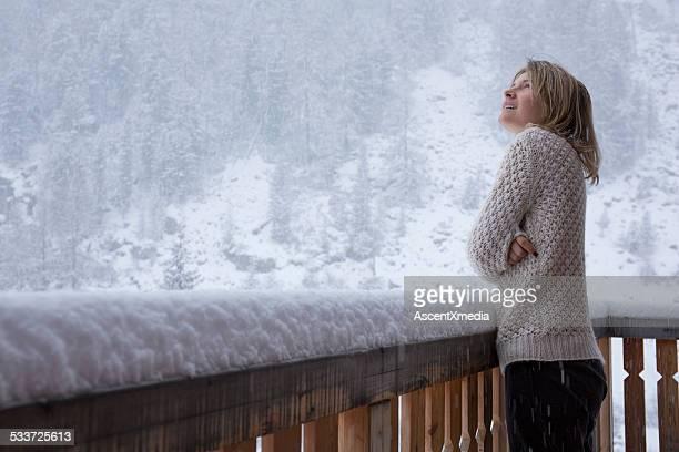 Jeune femme se dresse sur la terrasse, les montres flocons de neige pendant l'automne