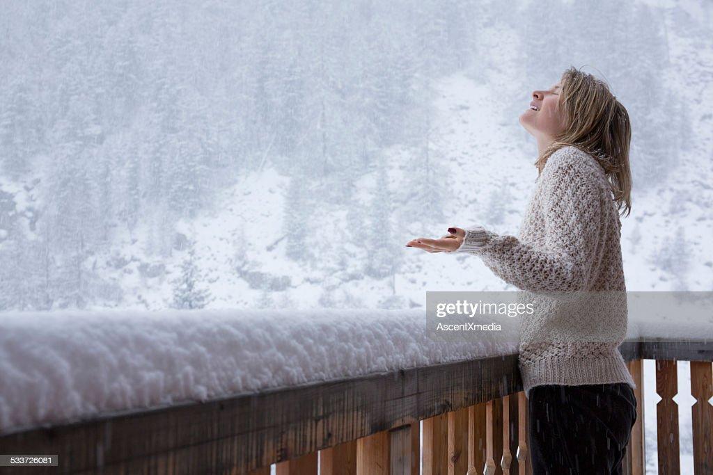 Giovane donna si trova sul ponte, orologi e fiocchi di neve cadere durante nevi : Foto stock