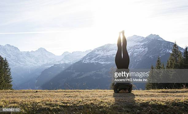 Young woman stands on head, snowy mountains behind