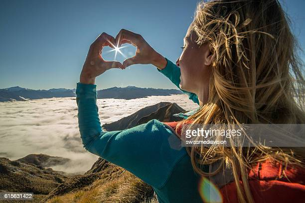 Young woman stands on mountain peak, frames sunbeam