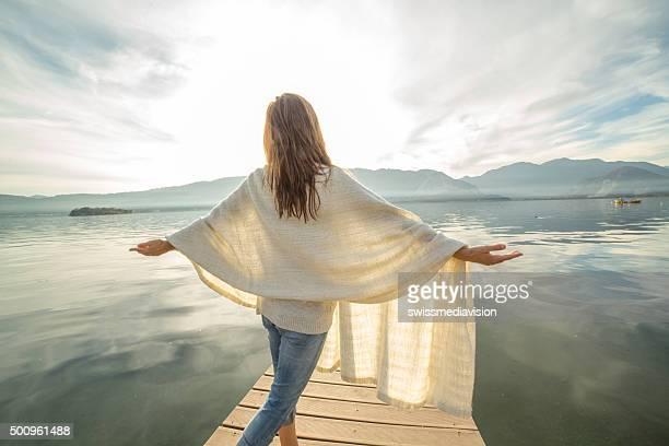 Jeune femme se dresse sur le pier bras tendus, relaxe