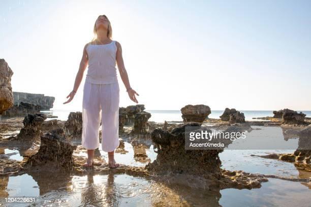 giovane donna si trova su affondo di roccia e guarda al mare - purezza foto e immagini stock