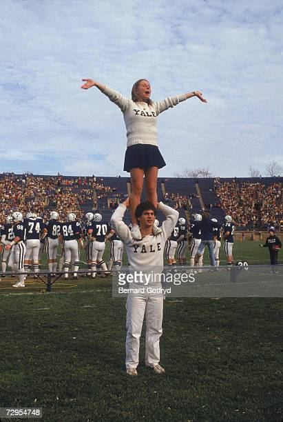 A young woman stands on the shoulders of a young man as they perform in their roles as Yale University cheeleaders at a football game Yale Bowl New...