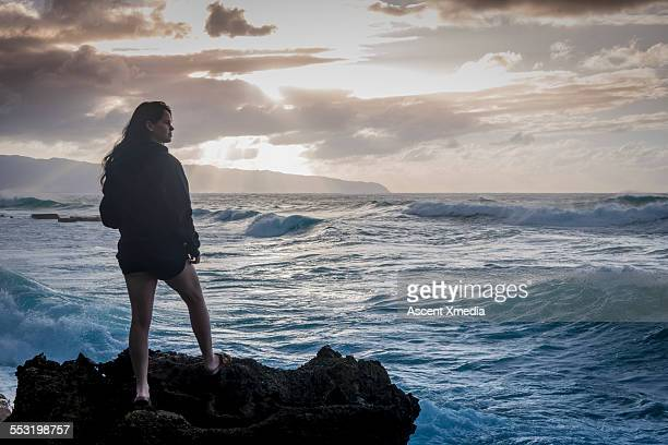 Young woman stands on tidal rocks, watches surf
