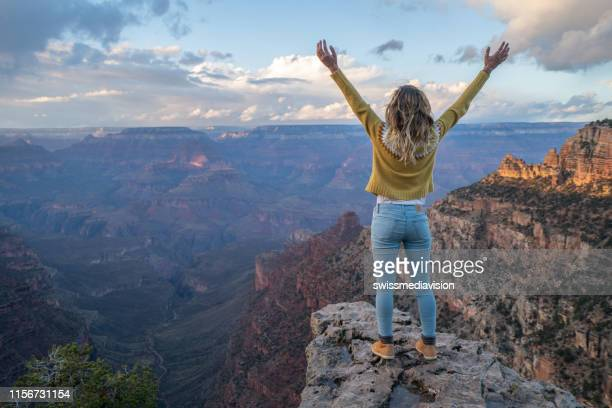 young woman stands on top of canyon embracing life and nature arms outstretched  girl enjoys hiking and travel usa - grand canyon national park stock pictures, royalty-free photos & images