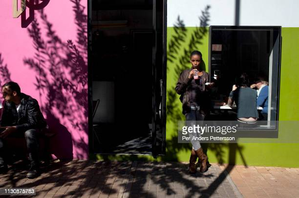 A young woman stands outside a popular cafe t on Juta street on May 26 2012 in Braamfontein in downtown Johannesburg South Africa The area is a...
