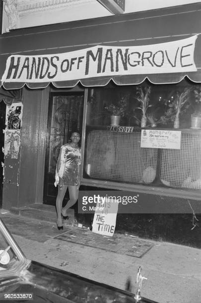 Young woman stands outside the Mangrove Caribbean restaurant in All Saints Road, Notting Hill, London on 10th August 1970. The restaurant, with a...