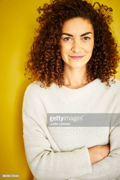 young woman stands with arms crossed facing the camera on a mustard yellow backdrop - smirking stock pictures, royalty-free photos & images