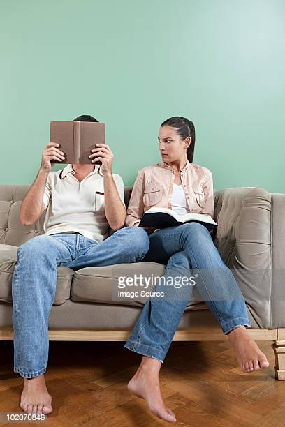 Jeune femme admirant un homme lisant sur un canapé